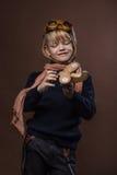 Το ευτυχές παιδί έντυσε στο πειραματικά καπέλο και τα γυαλιά Παιχνίδι παιδιών με το ξύλινο αεροπλάνο παιχνιδιών Έννοια ονείρου κα Στοκ Εικόνα