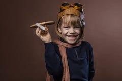 Το ευτυχές παιδί έντυσε στο πειραματικά καπέλο και τα γυαλιά Παιχνίδι παιδιών με το ξύλινο αεροπλάνο παιχνιδιών Έννοια ονείρου κα Στοκ Εικόνες