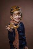 Το ευτυχές παιδί έντυσε στο πειραματικά καπέλο και τα γυαλιά Παιχνίδι παιδιών με το ξύλινο αεροπλάνο παιχνιδιών Έννοια ονείρου κα Στοκ εικόνες με δικαίωμα ελεύθερης χρήσης