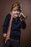 Το ευτυχές παιδί έντυσε στο πειραματικά καπέλο και τα γυαλιά Παιχνίδι παιδιών με το ξύλινο αεροπλάνο παιχνιδιών Έννοια ονείρου κα Στοκ φωτογραφία με δικαίωμα ελεύθερης χρήσης