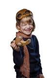 Το ευτυχές παιδί έντυσε στο πειραματικά καπέλο και τα γυαλιά Παιχνίδι παιδιών με το ξύλινο αεροπλάνο παιχνιδιών Έννοια ονείρου κα Στοκ εικόνα με δικαίωμα ελεύθερης χρήσης