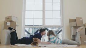 Το ευτυχές παντρεμένο ζευγάρι βάζει μεταξύ ανοίγει τα κιβώτια σε ένα καινούργιο σπίτι απόθεμα βίντεο