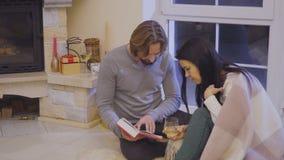 Το ευτυχές παντρεμένο ζευγάρι που διαβάζεται τη χαλάρωση βιβλίων κοντά στην εστία απόθεμα βίντεο