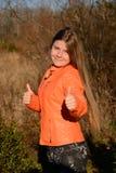 Το ευτυχές πεζοποριες κορίτσι που παρουσιάζει αντίχειρες υπογράφει επάνω Στοκ Εικόνα