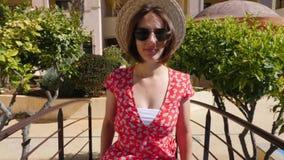 Το ευτυχές περπάτημα γυναικών χαμόγελου καυκάσιο προς τη κάμερα που φορά το κόκκινο φόρεμα και τα γυαλιά ηλίου στο φοίνικα ξενοδο απόθεμα βίντεο