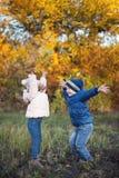 Το ευτυχές περπάτημα παιδιών υπαίθριο στο πάρκο φθινοπώρου ρίχνει τα φύλλα στοκ εικόνες