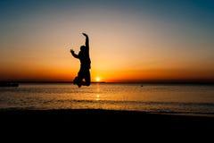 το ευτυχές πηδώντας άτομο χεριών έννοιας αύξησε τη νίκη σκιαγραφιών στοκ φωτογραφία