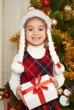 Το ευτυχές πορτρέτο κοριτσιών στη διακόσμηση Χριστουγέννων, έννοια χειμερινών διακοπών, διακόσμησε το δέντρο έλατου και τα δώρα στοκ εικόνες