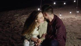 Το ευτυχές ρομαντικό ζεύγος κάθεται στην άμμο στην παραλία βραδιού σε ένα υπόβαθρο του ντεκόρ με τους ελαφριούς λαμπτήρες απόθεμα βίντεο