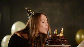 Το ευτυχές συναισθηματικό κορίτσι εκρήγνυται τα κεριά κατά τη διάρκεια του εορτασμού τα γενέθλιά της και επιδοκιμάζει Κλείστε επά απόθεμα βίντεο