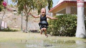 Το ευτυχές υγρό ξυπόλυτο κορίτσι στο φόρεμα πηδά στη λακκούβα στο πάρκ απόθεμα βίντεο