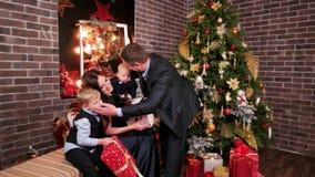Το ευτυχές φιλί παραμονής, συζύγων και συζύγων οικογενειακού νέο έτους ` s, γονείς που αγκαλιάζει τα παιδιά, οικογένεια, συγχαίρε απόθεμα βίντεο