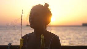 Το ευτυχές φυσώντας σαπούνι γυναικών brunette βράζει στο κρουαζιερόπλοιο στο όμορφο ηλιοβασίλεμα στη θάλασσα Στοκ Εικόνα