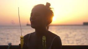 Το ευτυχές φυσώντας σαπούνι γυναικών brunette βράζει στο κρουαζιερόπλοιο στο όμορφο ηλιοβασίλεμα στη θάλασσα κίνηση αργή 3840x216 απόθεμα βίντεο