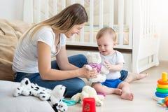 Το ευτυχές χαμογελώντας αγόρι μικρών παιδιών που παίρνει μαλακό teddy αντέχει το παιχνίδι από τη μητέρα Στοκ φωτογραφία με δικαίωμα ελεύθερης χρήσης