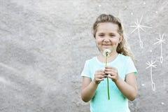 Το ευτυχές χαμογελώντας κορίτσι σε μια ελαφριά μπλούζα κρατά μια πικραλίδα στα χέρια της και κάνει μια επιθυμία ενάντια σε έναν θ στοκ εικόνα με δικαίωμα ελεύθερης χρήσης