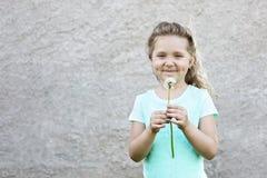 Το ευτυχές χαμογελώντας κορίτσι σε μια ελαφριά μπλούζα κρατά μια πικραλίδα στα χέρια της και κάνει μια επιθυμία ενάντια σε έναν θ στοκ φωτογραφία με δικαίωμα ελεύθερης χρήσης