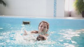 Το ευτυχές χαμογελώντας μικρό παιδί πηδά και βουτά κάτω από το νερό στην πισίνα Ένας υποβρύχιος πυροβολισμός Σε αργή κίνηση φιλμ μικρού μήκους