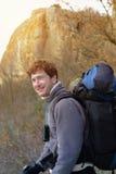 Το ευτυχές χαμογελώντας άτομο οδοιπόρων με το σακίδιο πλάτης στηρίζεται το φθινόπωρο μ Στοκ Φωτογραφία