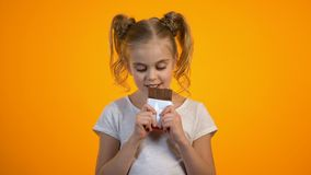Το ευτυχές χαμόγελο το κορίτσι που τρώει την εύγευστη σοκολάτα, απολαμβάνοντας το γλυκό γούστο φιλμ μικρού μήκους