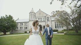 Το ευτυχές χαμόγελο newlyweds περπατά κοντά στο όμορφο μέγαρο την ηλιόλουστη ημέρα φιλμ μικρού μήκους