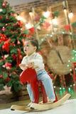Το ευτυχές χαριτωμένο μικρό αγόρι που οδηγά το ξύλινο άλογο λικνίσματος μπροστά από το χριστουγεννιάτικο δέντρο και παρουσιάζει σ Στοκ Εικόνα