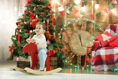 Το ευτυχές χαριτωμένο μικρό αγόρι που οδηγά το ξύλινο άλογο λικνίσματος μπροστά από το χριστουγεννιάτικο δέντρο και παρουσιάζει σ Στοκ Φωτογραφία