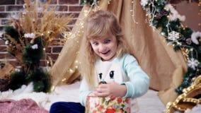 Το ευτυχές χαριτωμένο ξανθό μικρό κορίτσι βρίσκεται και θέτει με μια μάσκα φιλμ μικρού μήκους