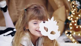 Το ευτυχές χαριτωμένο ξανθό μικρό κορίτσι βρίσκεται και θέτει με μια μάσκα απόθεμα βίντεο