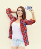 Το ευτυχές όμορφο κορίτσι φορά ένα ελεγμένο κόκκινο πουκάμισο και τα σορτς κάνουν το μόνος-πορτρέτο στο smartphone Στοκ εικόνα με δικαίωμα ελεύθερης χρήσης