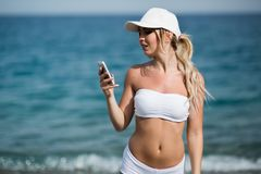 Το ευτυχές όμορφο ξανθό κορίτσι ικανότητας παρουσιάζει το κινητό τηλέφωνο και χαμόγελο Στοκ εικόνα με δικαίωμα ελεύθερης χρήσης