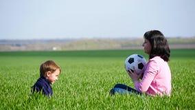 Το ευτυχές mom και ο γιος της κάθονται στην πράσινη χλόη και παίζουν με τη σφαίρα, ρίχνοντας το το ένα στο άλλο απόθεμα βίντεο