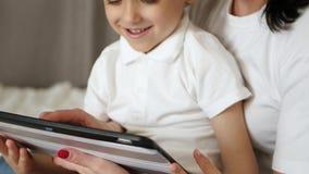 Το ευτυχές mom και το παιδί της ξοδεύουν το χρόνο στην ταμπλέτα στο σπίτι, τα κινούμενα σχέδια παιχνιδιού και προσοχής, παίζοντας απόθεμα βίντεο