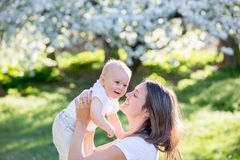 Το ευτυχές mom, που κρατά το χαριτωμένο αγοράκι της σταθμεύει την άνοιξη Στοκ εικόνα με δικαίωμα ελεύθερης χρήσης