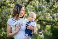 Το ευτυχές mom, που κρατά το χαριτωμένο αγοράκι της σταθμεύει την άνοιξη Στοκ εικόνες με δικαίωμα ελεύθερης χρήσης