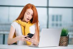 Το ευτυχές redhead κορίτσι στέλνει ένα μήνυμα sms στο φίλο εργαζόμενο στο σύγχρονο γραφείο Στοκ Εικόνα