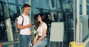 Το ευτυχές smartphone χρησιμοποίησης ζευγών ερωτευμένο, ακούει τη μουσική και τη συζήτηση ο ένας στον άλλο Νέο παντρεμένο ζευγάρι απόθεμα βίντεο