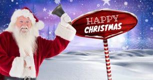 Το ευτυχή κείμενο Χριστουγέννων και το κουδούνι εκμετάλλευσης Santa με ξύλινο καθοδηγούν στο χειμερινό τοπίο Χριστουγέννων Στοκ εικόνες με δικαίωμα ελεύθερης χρήσης