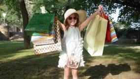 Το ευτυχή ψωνίζοντας, χαμογελώντας μικρό κορίτσι στα γυαλιά και το καπέλο αύξησαν τα χέρια με τις συσκευασίες μετά από τις επισκέ φιλμ μικρού μήκους
