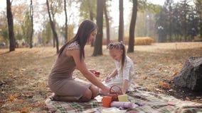 Το ευτυχείς mom και η κόρη έχουν τη διασκέδαση στο πάρκο πόλεων Η οικογένεια γελά και κάνει ταχυδακτυλουργίες τα μήλα ο ένας στον απόθεμα βίντεο