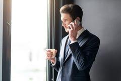 Το ευχάριστο σκεπτικό άτομο στέκεται με το smartphone Στοκ Εικόνα