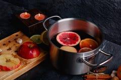 Το ευώδες θερμαμένο κρασί, δίπλα σε έναν πίνακα με τις φέτες των μήλων, των ραβδιών κανέλας, και των διακοσμητικών καίγοντας κερι Στοκ Φωτογραφίες