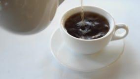 Το ευώδες μαύρο τσάι καυτό χύνεται από teapot απόθεμα βίντεο