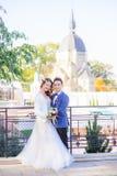 Το ευλογημένο γαμήλιο ζεύγος θέτει στη γέφυρα πριν από τον παλαιό καθεδρικό ναό Στοκ Φωτογραφία