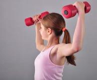 Το εφηβικό αθλητικό κορίτσι κάνει τις ασκήσεις για να αναπτύξει τους μυς στο γκρίζο υπόβαθρο Έννοια αθλητικού υγιής τρόπου ζωής Φ Στοκ φωτογραφίες με δικαίωμα ελεύθερης χρήσης