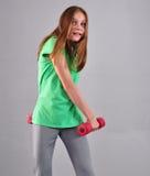 Το εφηβικό αθλητικό κορίτσι κάνει τις ασκήσεις για να αναπτύξει τους μυς στο γκρίζο υπόβαθρο Έννοια αθλητικού υγιής τρόπου ζωής Φ Στοκ εικόνα με δικαίωμα ελεύθερης χρήσης