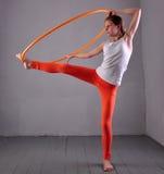 Το εφηβικό αθλητικό κορίτσι κάνει τις ασκήσεις με τη στεφάνη τ hula στο γκρίζο υπόβαθρο Κατοχή του παίζοντας παιχνιδιού διασκέδασ Στοκ εικόνες με δικαίωμα ελεύθερης χρήσης