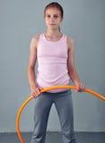 Το εφηβικό αθλητικό κορίτσι κάνει τις ασκήσεις με τη στεφάνη hula για να αναπτύξει το μυ στο γκρίζο υπόβαθρο Κατοχή της hula-στεφ Στοκ Εικόνες