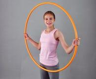 Το εφηβικό αθλητικό κορίτσι κάνει τις ασκήσεις με τη στεφάνη hula για να αναπτύξει το μυ στο γκρίζο υπόβαθρο Κατοχή του παίζοντας Στοκ Εικόνες