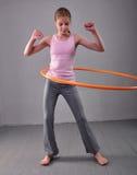 Το εφηβικό αθλητικό κορίτσι κάνει τις ασκήσεις με τη στεφάνη hula για να αναπτύξει το μυ στο γκρίζο υπόβαθρο Κατοχή του παίζοντας Στοκ Φωτογραφίες